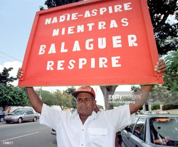 Dominican party loyalist of Joaquin Balaguer stands May 8 2000 outside the house of veteran political leader in Santo Domingo Dominican Republic The...