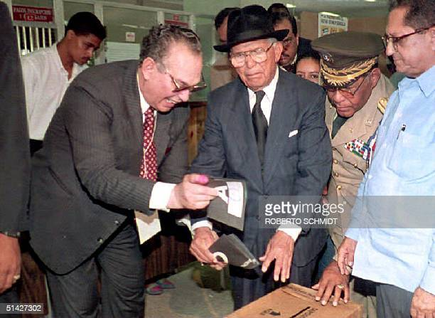 Dominican President Joaquin Balaguer who is almost completely blind is assisted by his personal aid as he casts his ballot 16 May 1994 at a local...