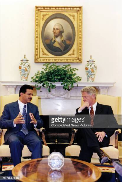 Dominican President Leonel Fernandez and US President Bill Clinton talk together in the White House's Oval Office Washington DC June 10 1998