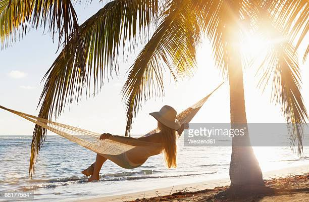 dominican rebublic, young woman in hammock looking out over tropical beach - mar dei caraibi foto e immagini stock
