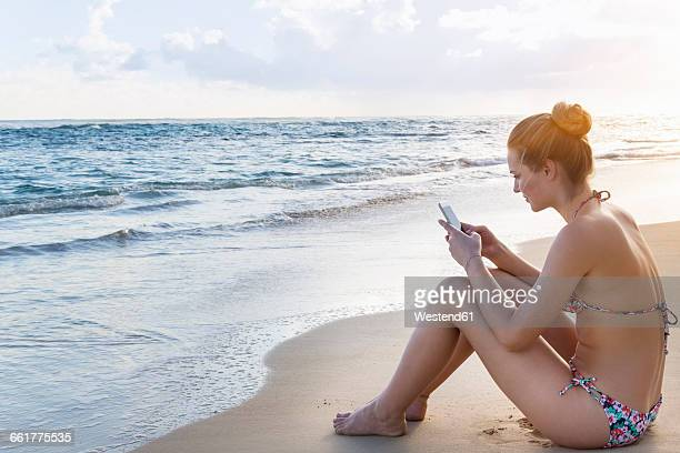 Dominican Rebublic, Young woman on tropical beach using mobile device