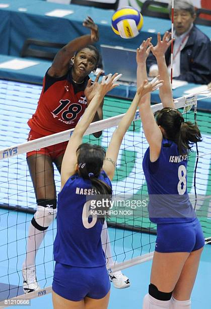 Dominican Republic attacker Bethania De La Cruz de Pena spikes the ball over Kazakhstan blockers Olga Nassedkina and Korinna Ishimtseva during their...
