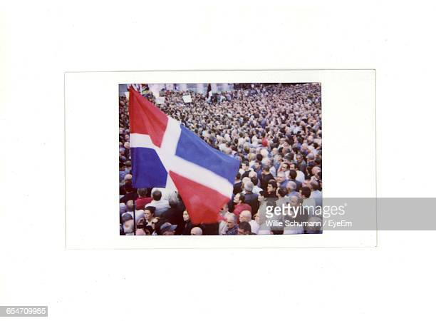 dominican republic flag above crowded street in city - dominican republic flag stock pictures, royalty-free photos & images
