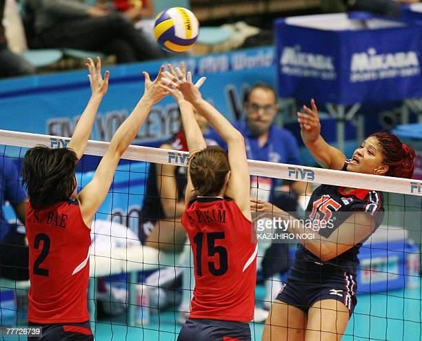 Dominican Republic's captain Cosiri Rodrigues Andino spikes the ball over South Korean blocker Bae Yoo-Na and Kim Se-Young during their second round...