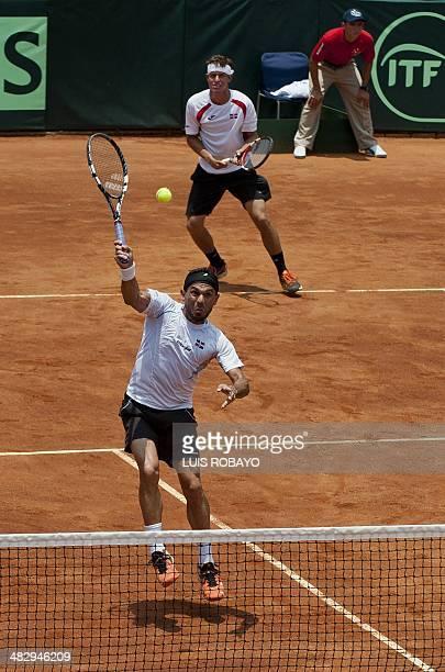 Dominican Republic's tennis player Victor Estrella returns the ball next to teammate Jose Hernandez to Colombian tennis player Robert Farah and Juan...
