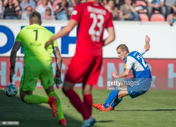 Dominick Drexler of Kiel scores his teams third goal against goalkeeper Kevin Mueller and Kevin Kraus of Heidenheim during the Second Bundesliga...