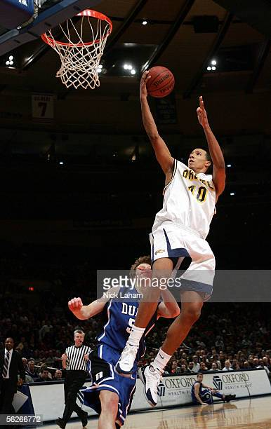 Dominick Meija of the Drexel Dragons goes in for a layup over Martynas Pocius of the Duke Blue Devils during their Preseason NIT game at Madison...