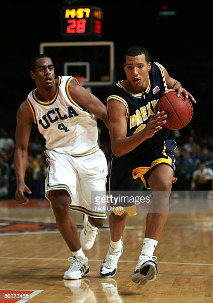 Dominick Mejia of the Drexel Dragons dribbles down the court in front of Arron Afflalo of the UCLA Bruins during their Preseason NIT Tournament game...
