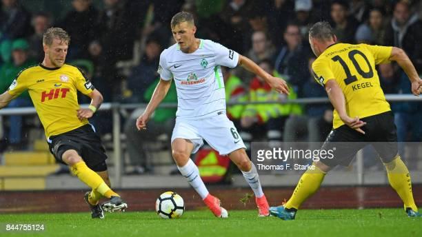 Dominik Ernst and Maik Kegel of Koeln tackle Dennis Rosin of Bremen during the 3 Liga match between SV Werder Bremen II and SC Fortuna Koeln at Platz...