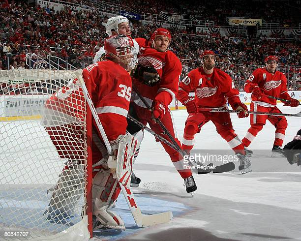 Dominik Hasek Nicklas Lidstrom Henrik Zetterberg and Pavel Datsyuk of the Detroit Red Wings look up to find the high flying puck during a game...