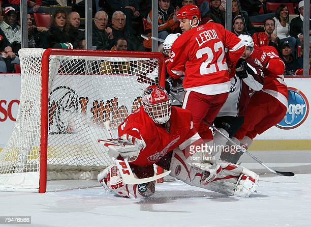 Dominik Hasek of the Detroit Red Wings makes a save as teammate Brett Lebda looks over his shoulder during a NHL game against the Colorado Avalanche...