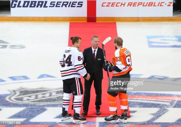 Dominik Hasek shakes hands with Jakub Voracek of the Philadelphia Flyers and David Kampf after a ceremonial face-off before the Global Series...