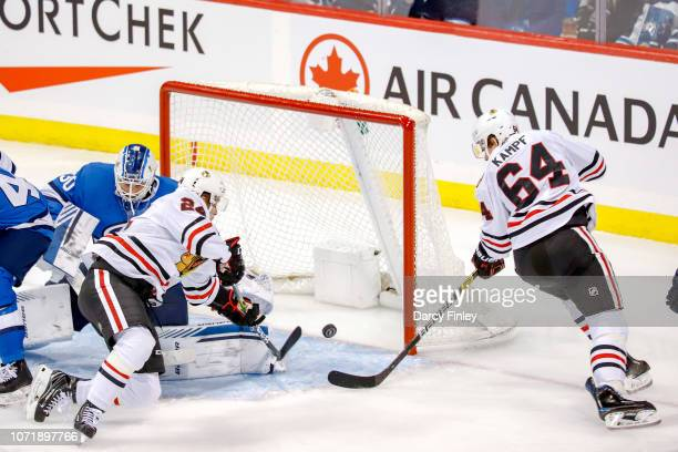 Dominik Kahun and David Kampf of the Chicago Blackhawks reach for the loose puck during a second period scramble in the crease against the Winnipeg...
