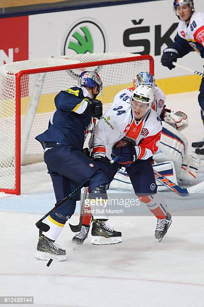 Dominik Kahun of Munich and Olli Palola of Vaxjo during the Champions Hockey League Round of 32 match between Red Bull Munich and Vaxjo Lakers at...