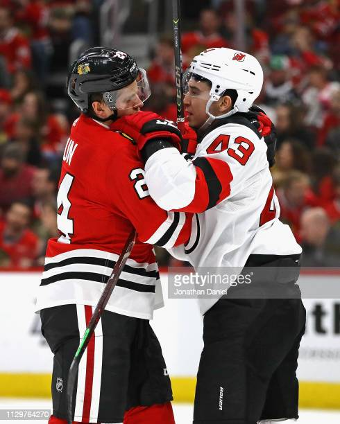 Dominik Kahun of the Chicago Blackhawks and Brett Seney of the New Jersey Devils get tangled up after a play in from of the Devils net at the United...