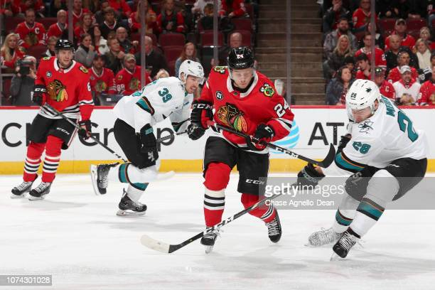 Dominik Kahun of the Chicago Blackhawks and Timo Meier of the San Jose Sharks get physical in the first period at the United Center on December 16...