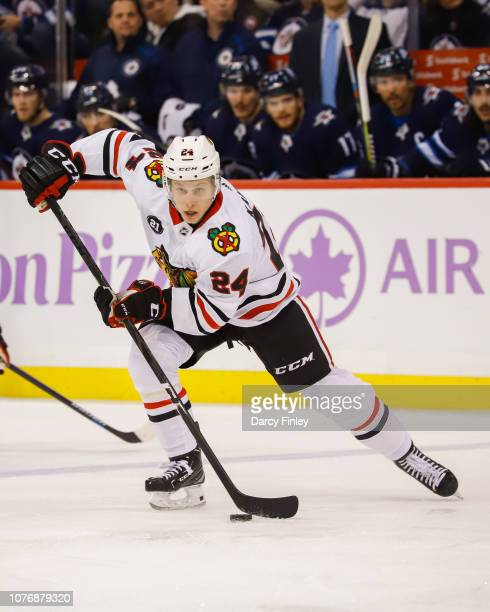 Dominik Kahun of the Chicago Blackhawks plays the puck down the ice during third period action against the Winnipeg Jets at the Bell MTS Place on...