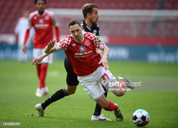 Dominik Kohr of 1. FSV Mainz 05 is tackled by Manuel Prietl of DSC Arminia Bielefeld during the Bundesliga match between 1. FSV Mainz 05 and DSC...