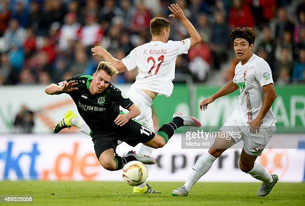 Dominik Kohr of Augsburg and JeongHo Hong of Augsburg compete with Felix Klaus of Hannover for the ball during the Bundesliga match between FC...