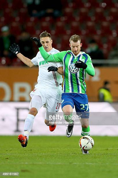 Dominik Kohr of Augsburg battles for the ball with Maximilian Arnold of Wolfsburg during the Bundesliga match between FC Augsburg and VfL Wolgsburg...