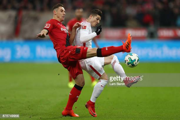 Dominik Kohr of Bayer Leverkusen fights for the ball with Marcel Sabitzer of Leipzig during the Bundesliga match between Bayer 04 Leverkusen and RB...