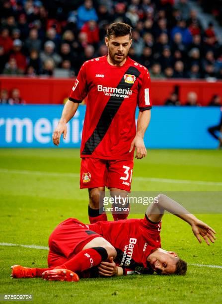 Dominik Kohr of Bayer Leverkusen lies injured infront of Kevin Volland of Bayer Leverkusen during the Bundesliga match between Bayer 04 Leverkusen...