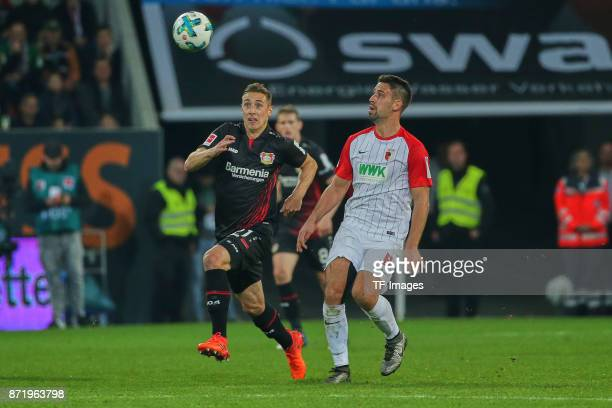 Dominik Kohr of Leverkusen and Rani Khedira of Augsburg battle for the ball during the Bundesliga match between FC Augsburg and Bayer 04 Leverkusen...