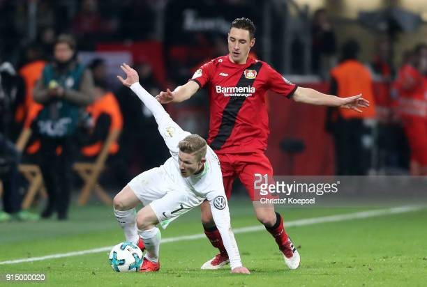 Dominik Kohr of Leverkusen challenges Florian Kainz of Bremen during the DFB Cup quarter final match between Bayer Leverkusen and Werder Bermen at...
