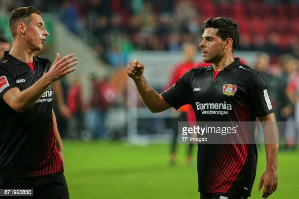 Dominik Kohr of Leverkusen shakes hands with Kevin Volland of Leverkusen during the Bundesliga match between FC Augsburg and Bayer 04 Leverkusen at...