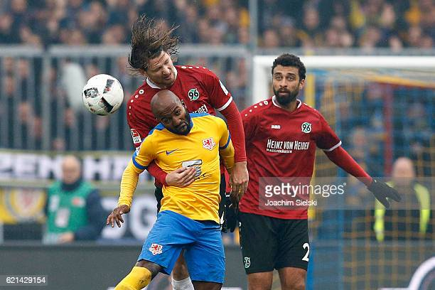 Dominik Kumbela of Braunschweig challenges Stefan Strandberg and Felipe Trevizan Martins of Hannover during the Second Bundesliga match between...