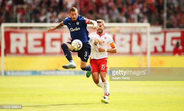 Dominik Schmidt of Holstein Kiel is chased by Marco Gruettner of Jahn Regensburg during the Second Bundesliga match between SSV Jahn Regensburg and...