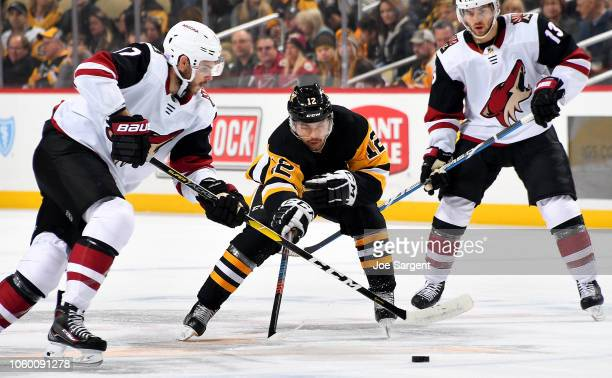 Dominik Simon of the Pittsburgh Penguins battles for the puck against Alex Galchenyuk of the Arizona Coyotes at PPG Paints Arena on November 10 2018...