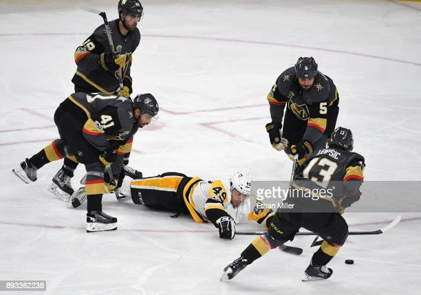 Dominik Simon of the Pittsburgh Penguins dives on the ice as he tries to control the puck against Alex Tuch PierreEdouard Bellemare Deryk Engelland...