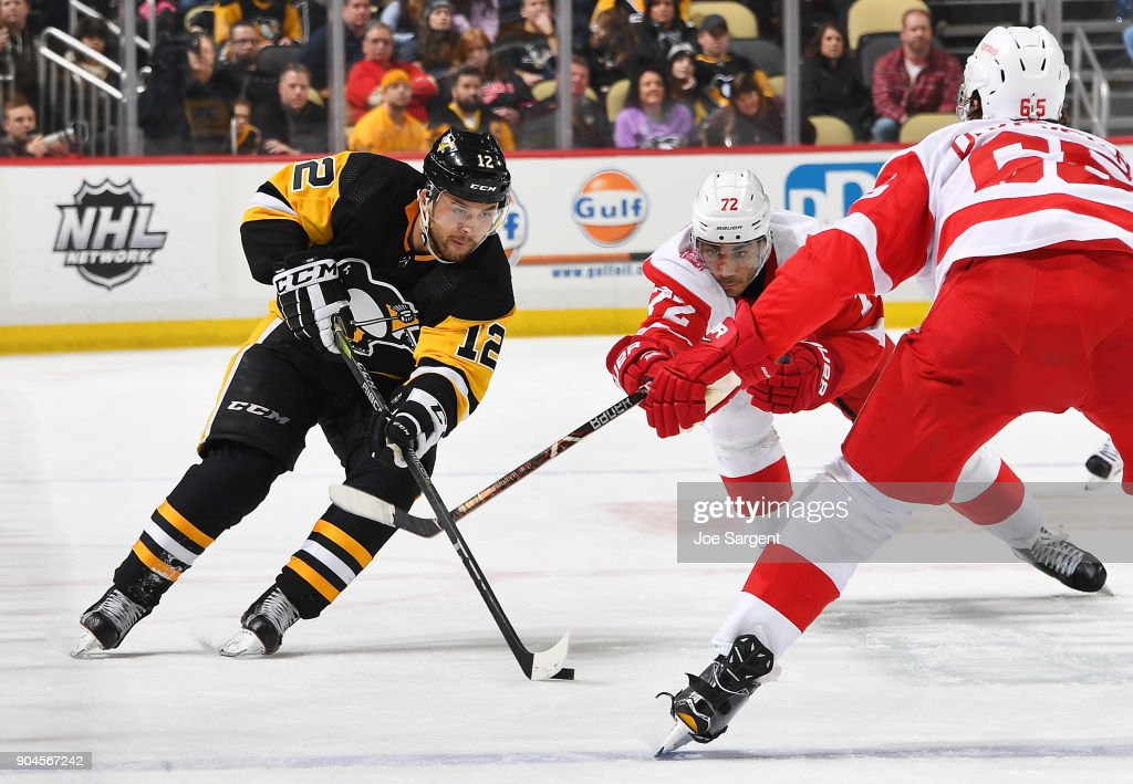 Dominik Simon #12 of the Pittsburgh Penguins handles the puck against Andreas Athanasiou #72 of the Detroit Red Wings at PPG Paints Arena on January 13, 2018 in Pittsburgh, Pennsylvania.