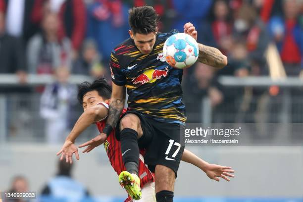 Dominik Szoboszlai of Leipzig battles for the ball with Wooyeong Jeong of Freiburg during the Bundesliga match between Sport-Club Freiburg and RB...