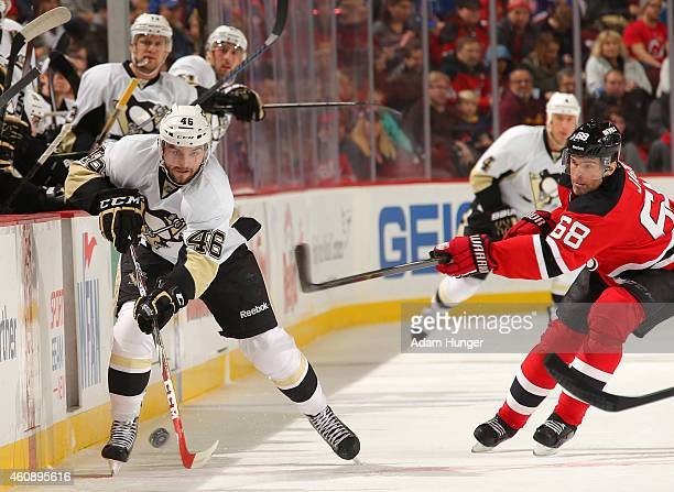 Dominik Uher of the Pittsburgh Penguins controls the puck in front of Jaromir Jagr of the New Jersey Devils during the first period at the Prudential...
