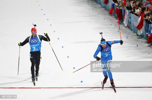 Dominik Windisch of Italy crosses the finish line ahead of Arnd Peiffer of Germany to win the bronze medal during the Biathlon 2x6km Women 2x75km Men...