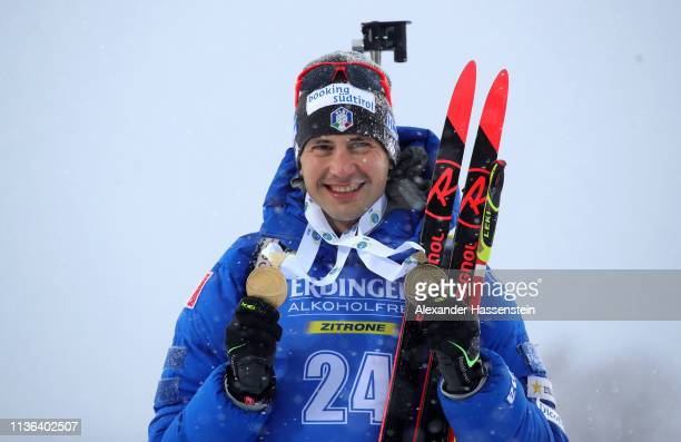 Dominik Windisch of Italy poses with his medals from the Championships following victory in the Men's Mass Start at the IBU Biathlon World...