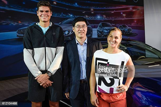 Dominika Cibulkova of Slovakia and Milos Raonic of Canada pose for a picture with a guest during an event at the Mercedes booth on day three of the...
