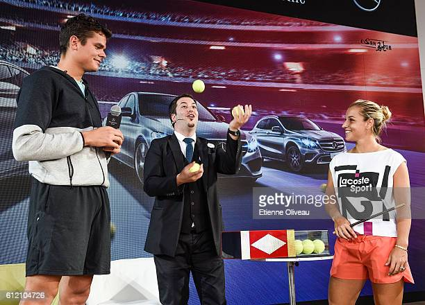 Dominika Cibulkova of Slovakia and Milos Raonic of Canada watch a magician during an event at the Mercedes booth on day three of the 2016 China Open...