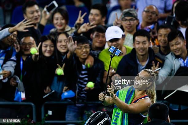 Dominika Cibulkova of Slovakia takes a selfie with fans after winning the women's singles third round match against Karolina Pliskova of the Czech...