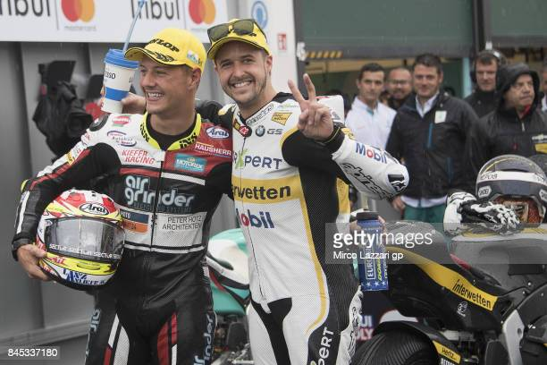 Dominique Aegerter of Switzerland and Kiefer Racing and Thomas Luthi of Switzerland and Carxpert Interwetten celebrate under the podium at the end of...