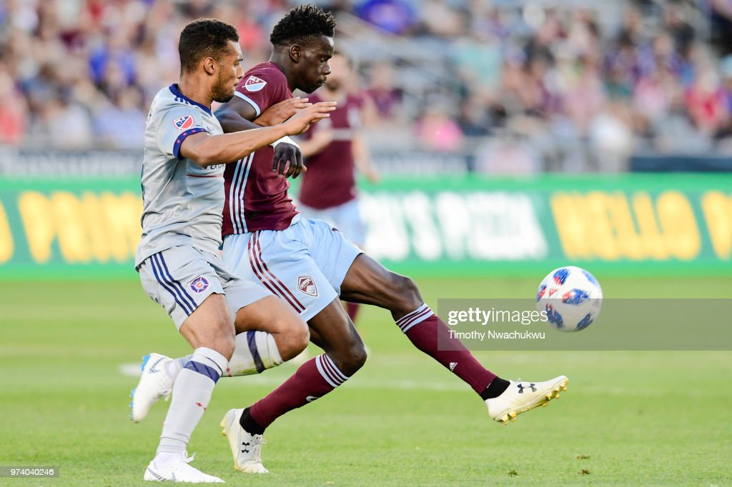 Dominique Badji #14 of Colorado Rapids tries to maintain possession by Johan Kappelhof #4 of Chicago Fire at Dick's Sporting Goods Park on June 13, 2018 in Commerce City, Colorado.