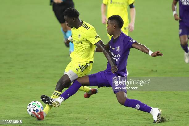 Dominique Badji of Nashville SC and Andres Perea of Orlando City SC fight for the ball during an MLS soccer match at Exploria Stadium on August 26,...
