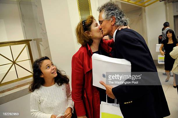 Dominique Bagnato, right, of France is greeted by his wife, Tesa Conlin, center, as daughter, Bliss Bagnato-Conlin left, looks on following a...