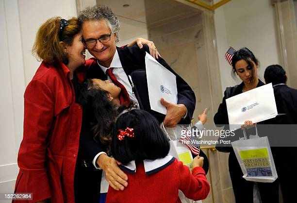 Dominique Bagnato, top center, of France is greeted by his wife, Tesa Conlin, left, and daughters, Bliss Bagnato-Conlin middle left center, and Mila...