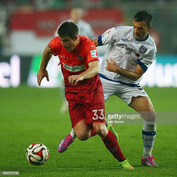 Dominique Heintz of Kaiserslautern is challenged by Edmond Kapllani of Frankfurt during the Second Bundesliga match between 1 FC Kaiserslautern and...