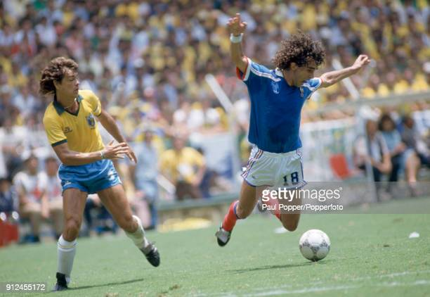 Dominique Rocheteau of France falling after a challenge by the Brazilian captain Edinho during the FIFA World Cup quarter final between France and...
