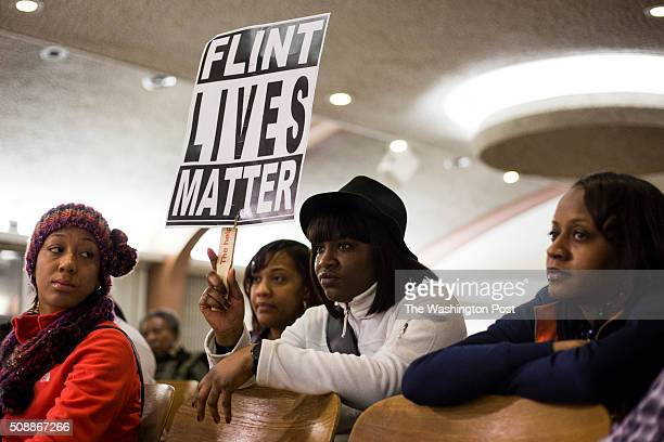 Dominique Strong Flint Mich holds up a sign during a city council meeting which introduced the topic of whether Flint residents should have to pay...