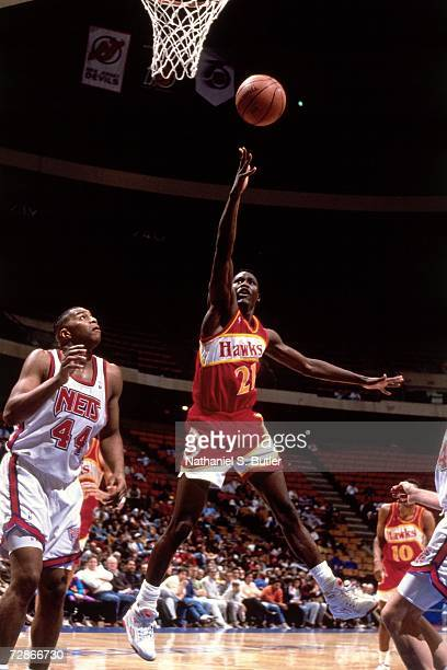 Dominique Wilkins of the Atlanta Hawks attempts a layup against Derrick Coleman of the New Jersey Nets during a 1990 NBA game played at Brendan Byrne...